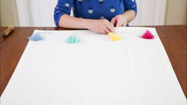Attaching tassels to a drop cloth rug
