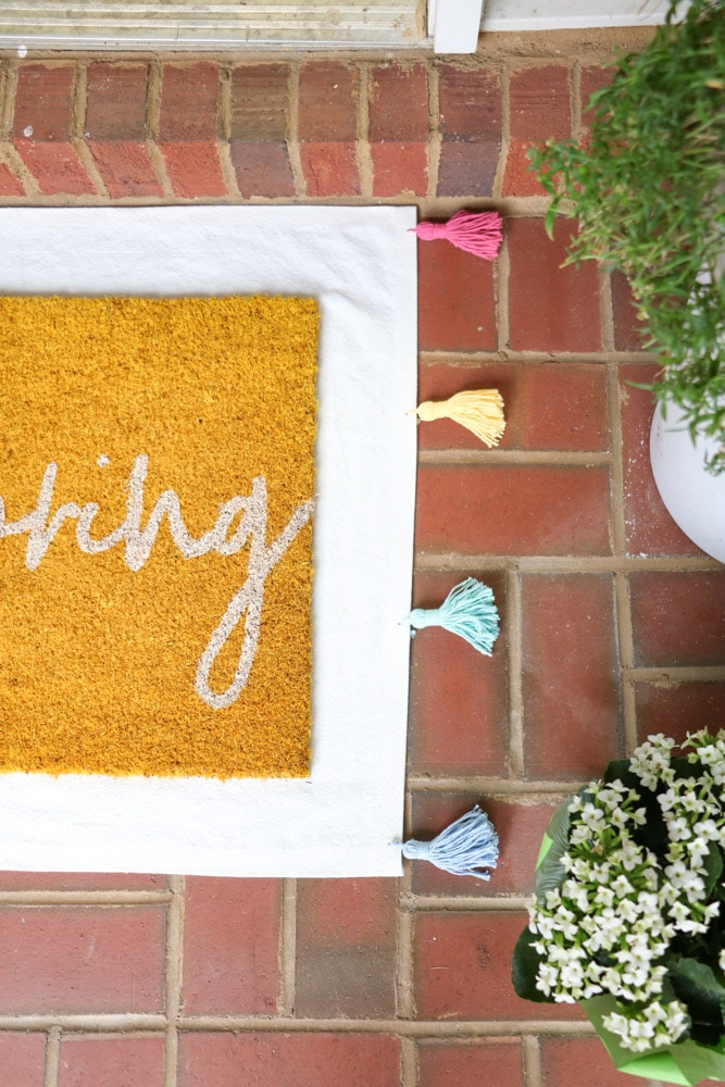 DIY drop cloth rug with rainbow colored tassels and layered with a yellow hello spring mat
