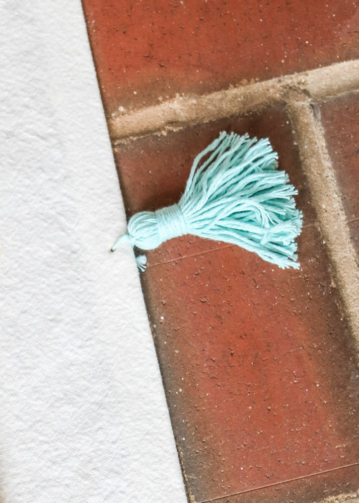 How to make a tassel with yarn example of a light teal tassel.