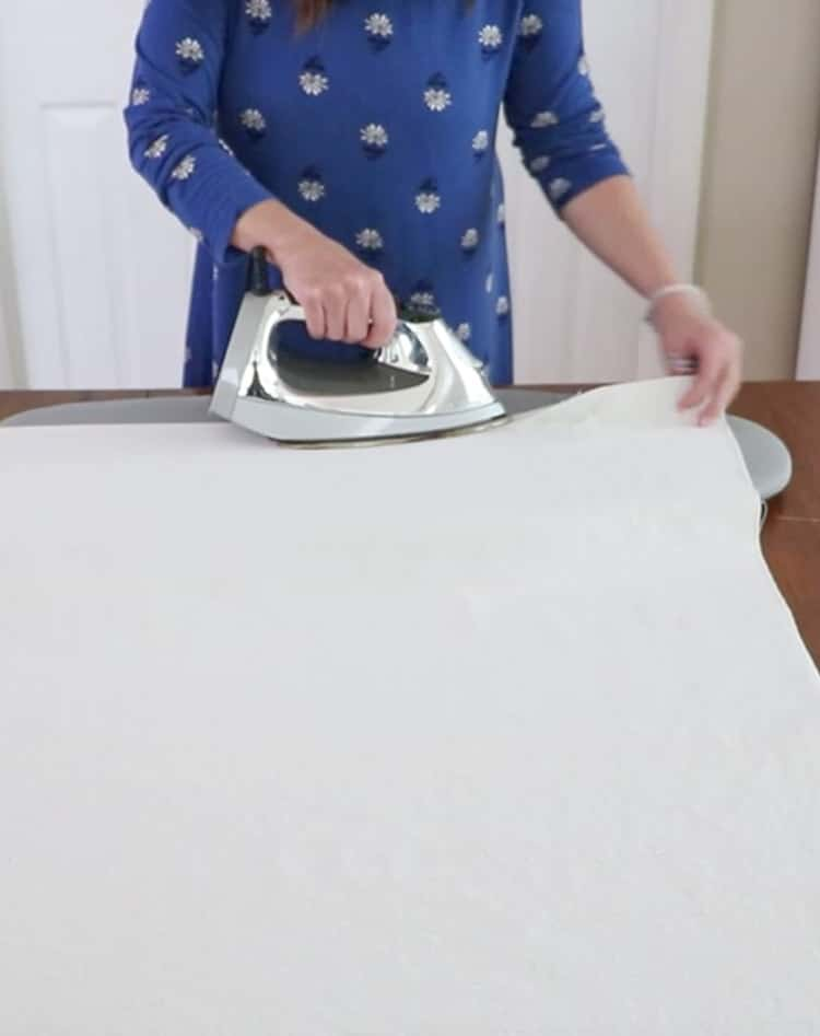 "How to make a drop cloth rug by turning the sides under 1"" and pressing the canvas."
