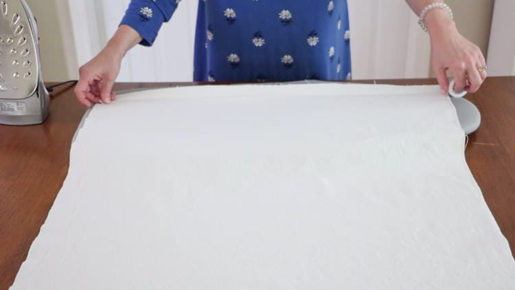 How to make a drop cloth rug by opening the folded canvas and measuring out a piece of no sew hem tape and cutting it to the length.