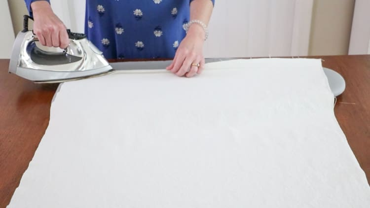How to make a drop cloth rug by folding the canvas over the iron on hem tape and pressing the iron down for 3 to 5 seconds to close the hem