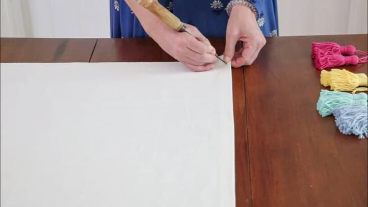 How to make a drop cloth rug by marking where you want your tassels to go and then making a hole with a sharp object like an ice pick.