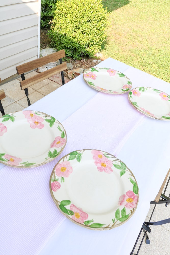 Garden party decoration ideas using white linen tablecloth, pink and white runner and desert rose dishes