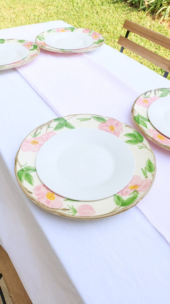 Garden party decoration ideas using white linen tablecloth, pink and white runner and desert rose dishes with a white salad plate in the middle