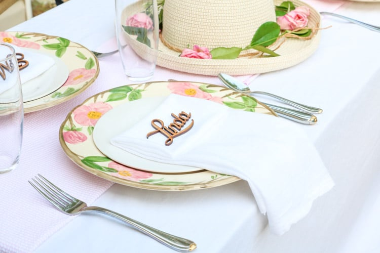 Garden party decoration ideas using white linen tablecloth, pink and white runner and desert rose dishes with a white salad plate in the middle with a folded linen napkin and a wooden laser cut name of guest.