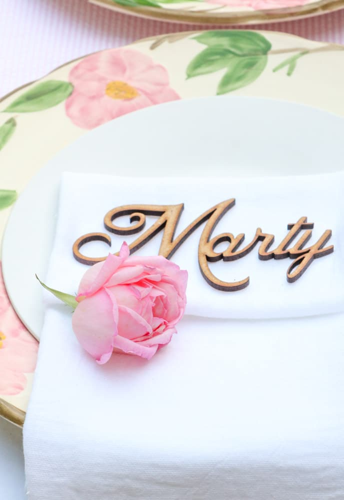 Garden party place setting idea with a pink rose on a white linen napkin sitting on a desert rose place and a white salad plate.