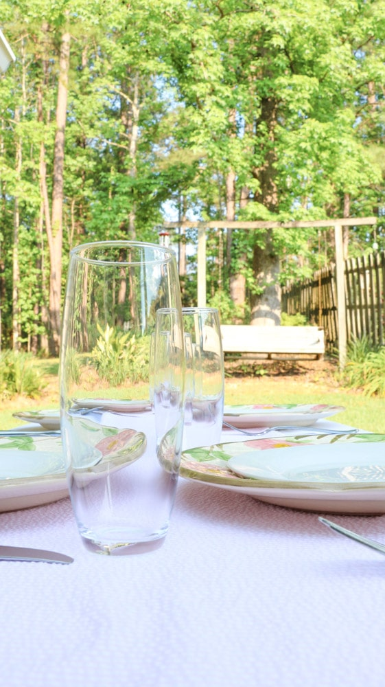 Garden party decoration ideas using white linen tablecloth, pink and white runner and desert rose dishes with a white salad plate in the middle.  Then add champagne glasses