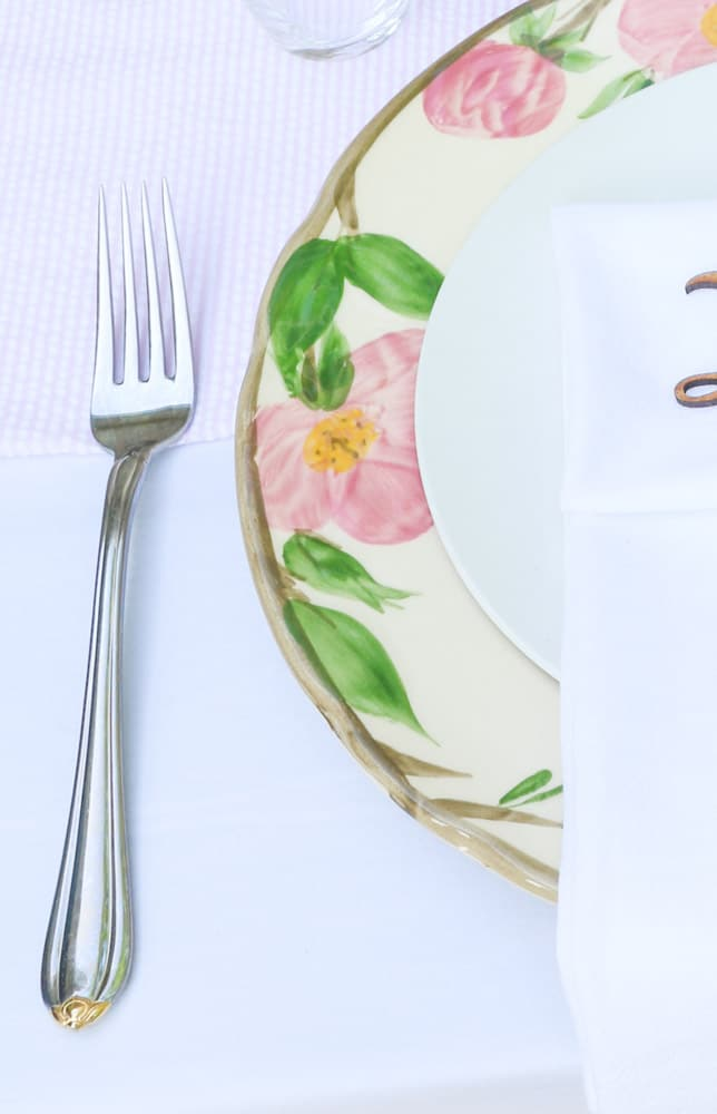 Garden party decoration ideas using white linen tablecloth, pink and white runner and desert rose dishes with a white salad plate in the middle.  Then add silverware.