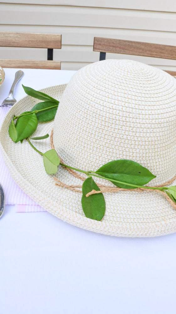 Garden party decoration ideas using a straw hat as a centerpiece with fresh green vine around the brim of the hat.