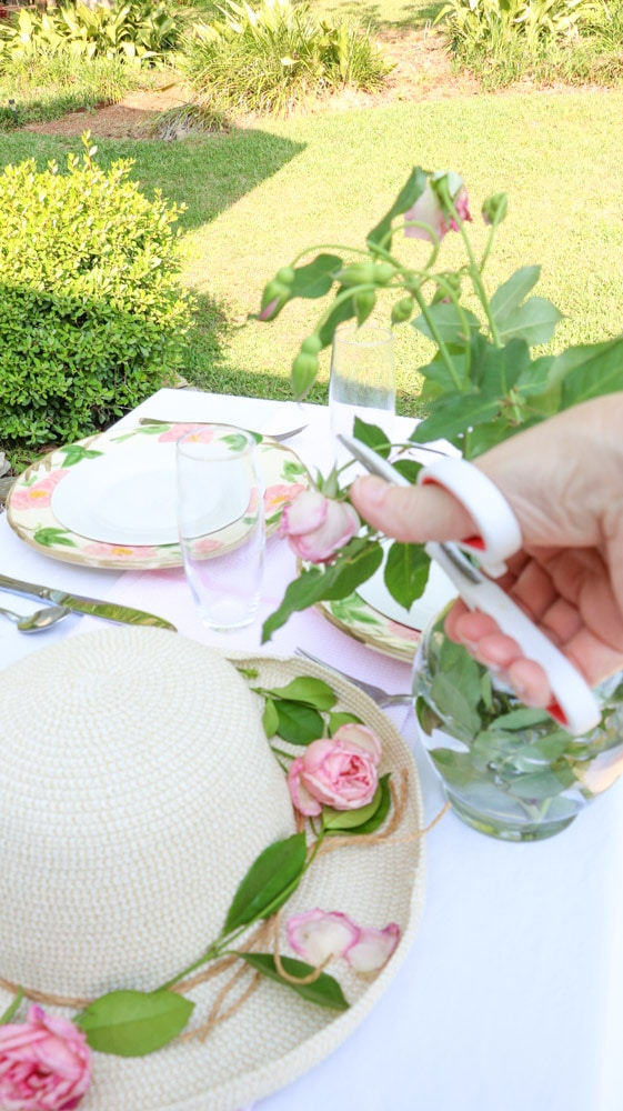 Garden party decoration ideas using a straw hat as a centerpiece with fresh green vine around the brim of the hat and fresh pink roses.
