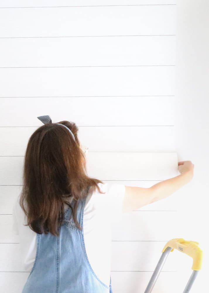 How to install peel and stick wallpaper on an accent wall with a shiplap wall covering.
