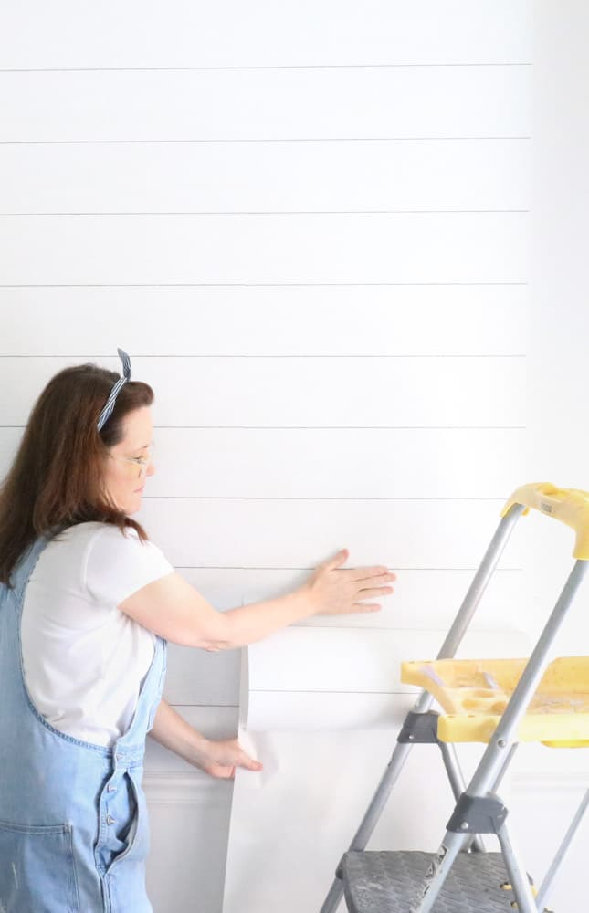 How to apply peel and stick wallpaper on an accent wall with a shiplap wall covering.