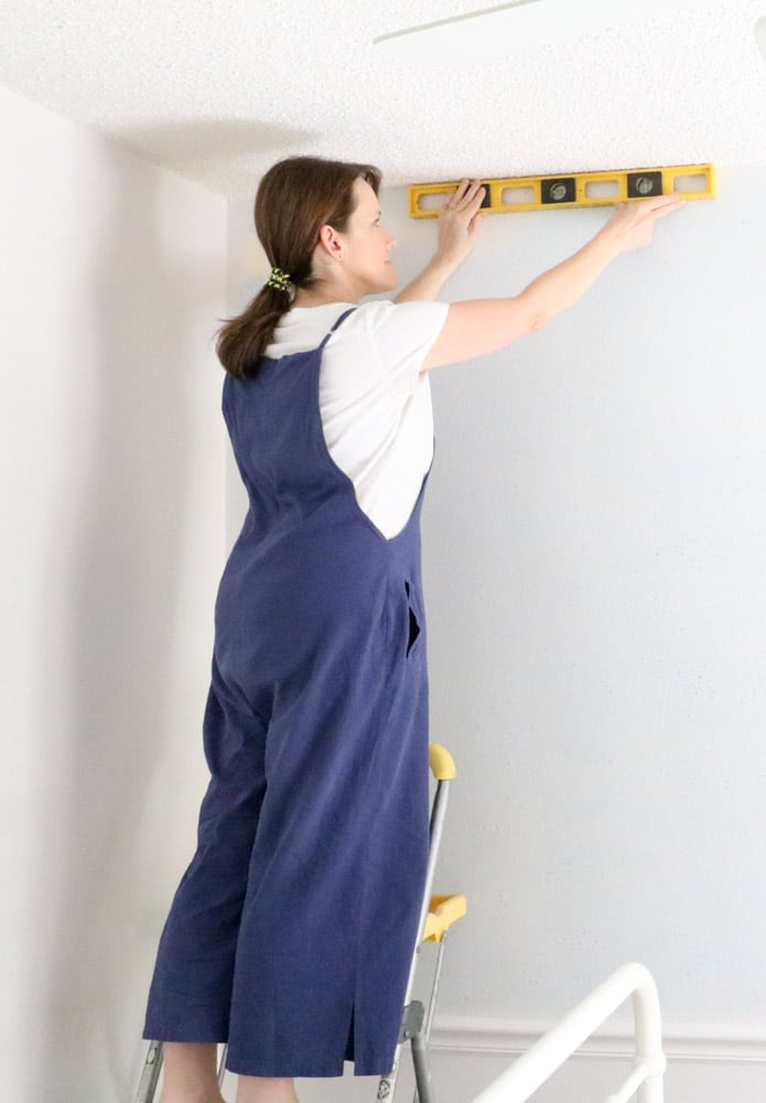 How to install peel and stick wallpaper by making sure the ceiling and wall are level first.