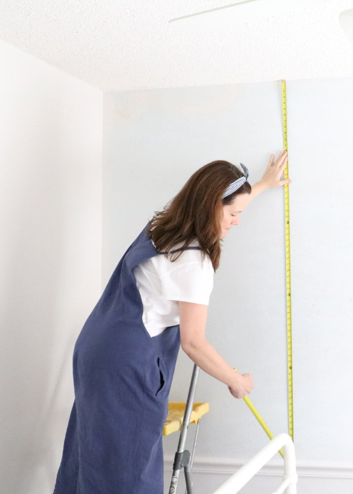 How to hang peel and stick wallpaper first by measuring the wall.