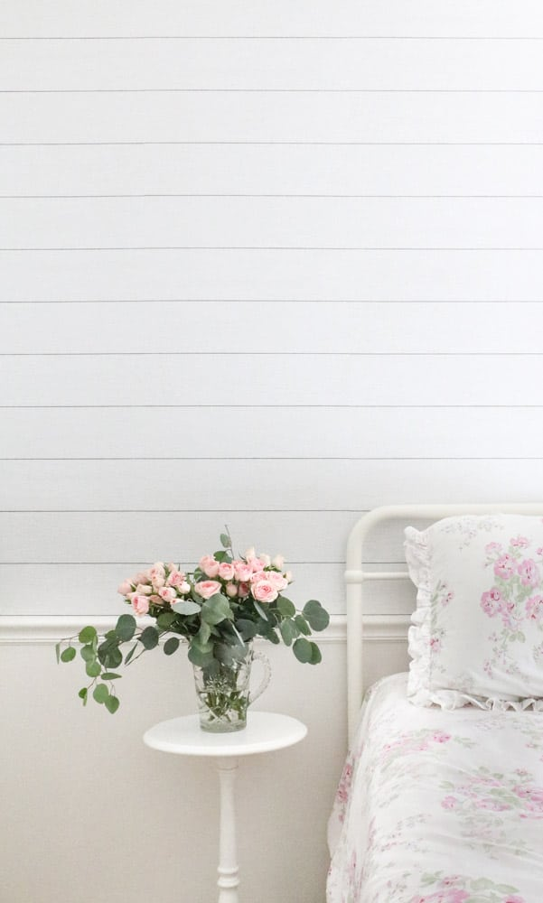Showing the paint finish on a wall in a bedroom that has a twin bed with a small white round nightstand that has roses on in a vase.  The chair rail and below are white with a shiplap peel and stick wallpaper on the top.