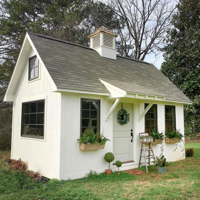 A white gardening she shed by Vintage Brick House