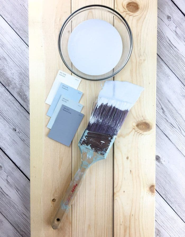 Paint brushes, swatches and a little paint on a board