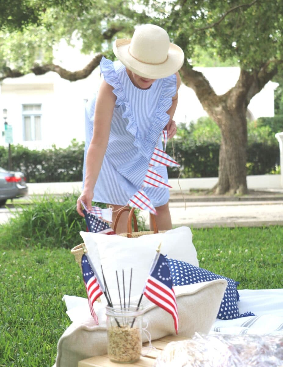Patriotic picnic ideas using layered blankets on the ground, stacking pillows up against baskets.  Decorations of red, white and blue banners, pillows and flags