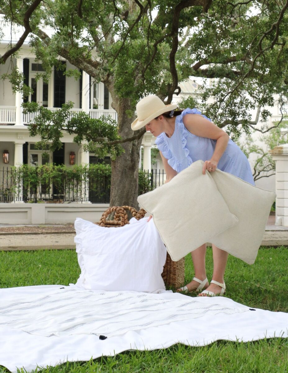 Patriotic picnic ideas using layered blankets on the ground, stacking pillows up against baskets.