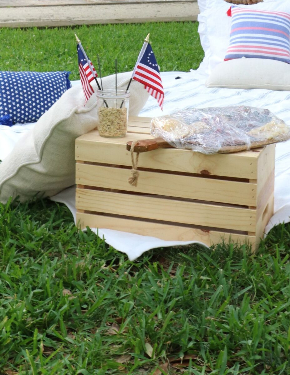 Fourth of July picnic ideas using a wooden crate turned upside down to act as a table.  Charcuterie board filled with food and a small mason jar filled with oatmeal that has two mini Betsy Ross flags inside.