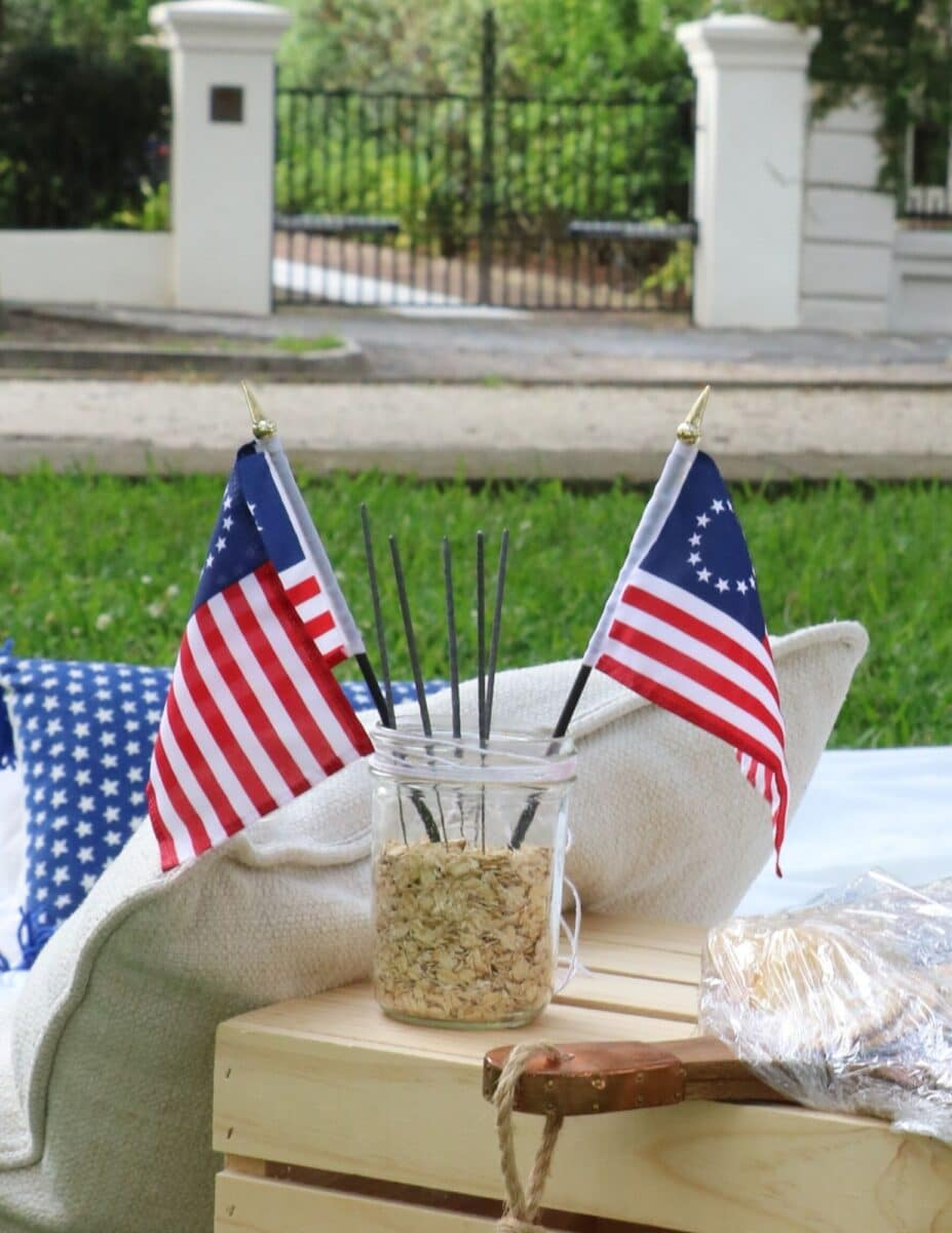 Patriotic picnic decorations of two Betsy Ross mini flags and sparklers sitting inside a mason jar filled with oatmeal