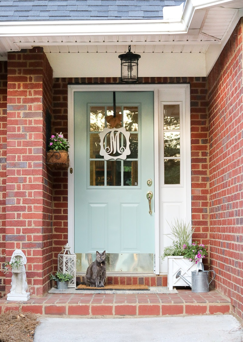 Small front porch decorating ideas with a layered rug, container garden of plants and flowers, watering can, statue of a dog holding flowers, and monogram wreath.