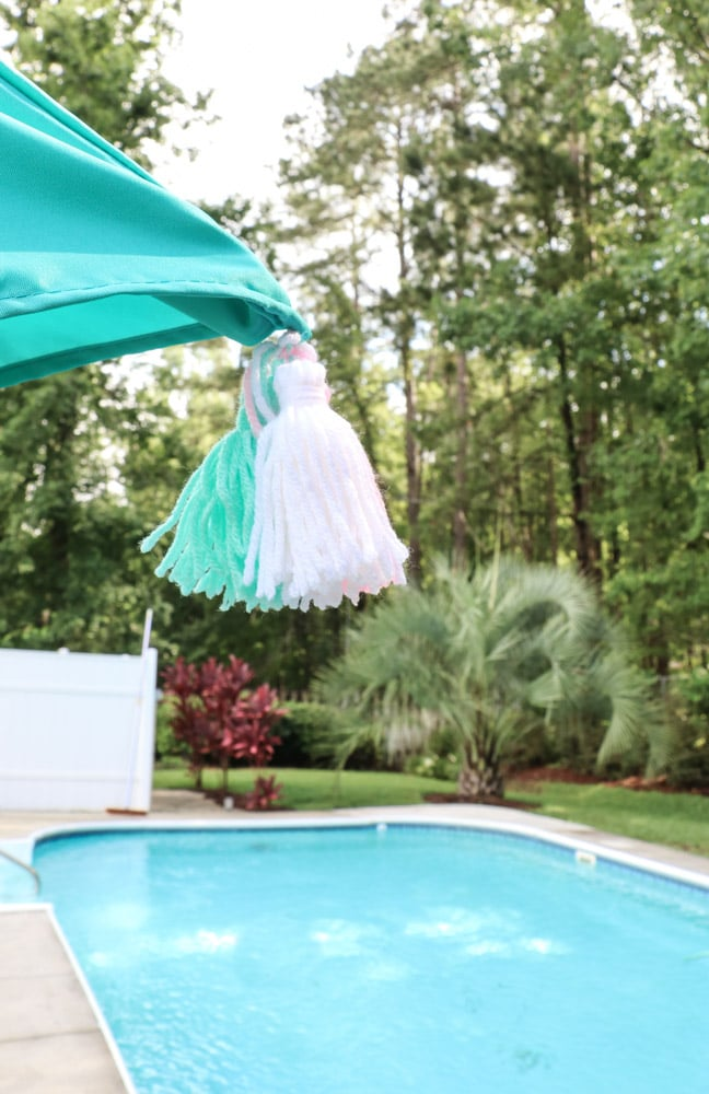 A backyard umbrella for your pool party with home-made tassels sewn into the bright blue umbrella.