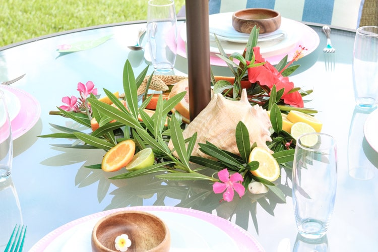 A Hawaiian tablescape with shells, cut citrus, shells, bright hibiscus flowers, a leaves.