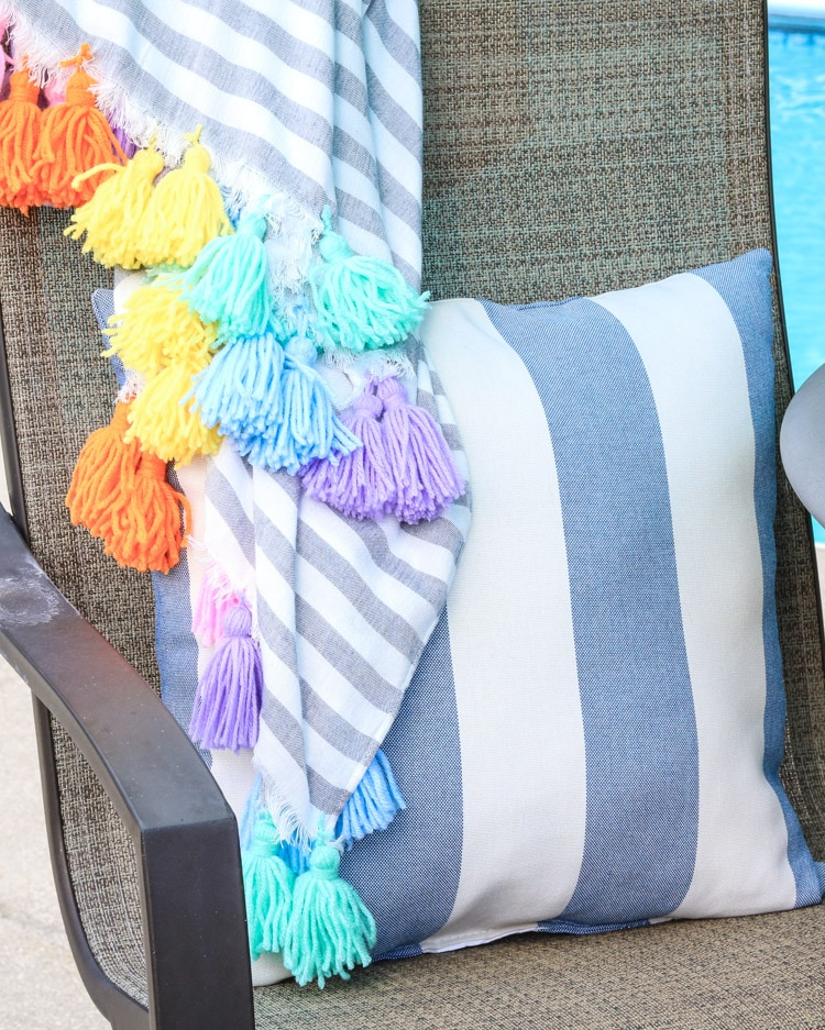 A Hawaiian themed decor idea including a bright colorful tassel blanket and a striped blue pillow.