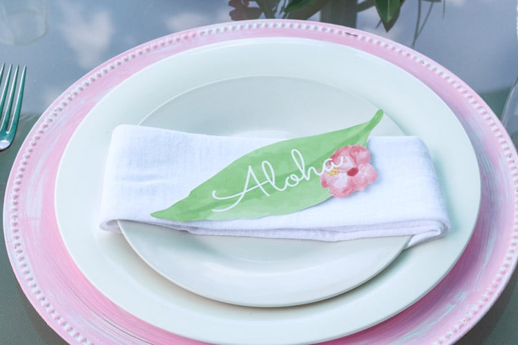 A Hawaiian table setting with a pink painted charger with a napkin wrapped salad plate with a leaf printable that says Aloha.