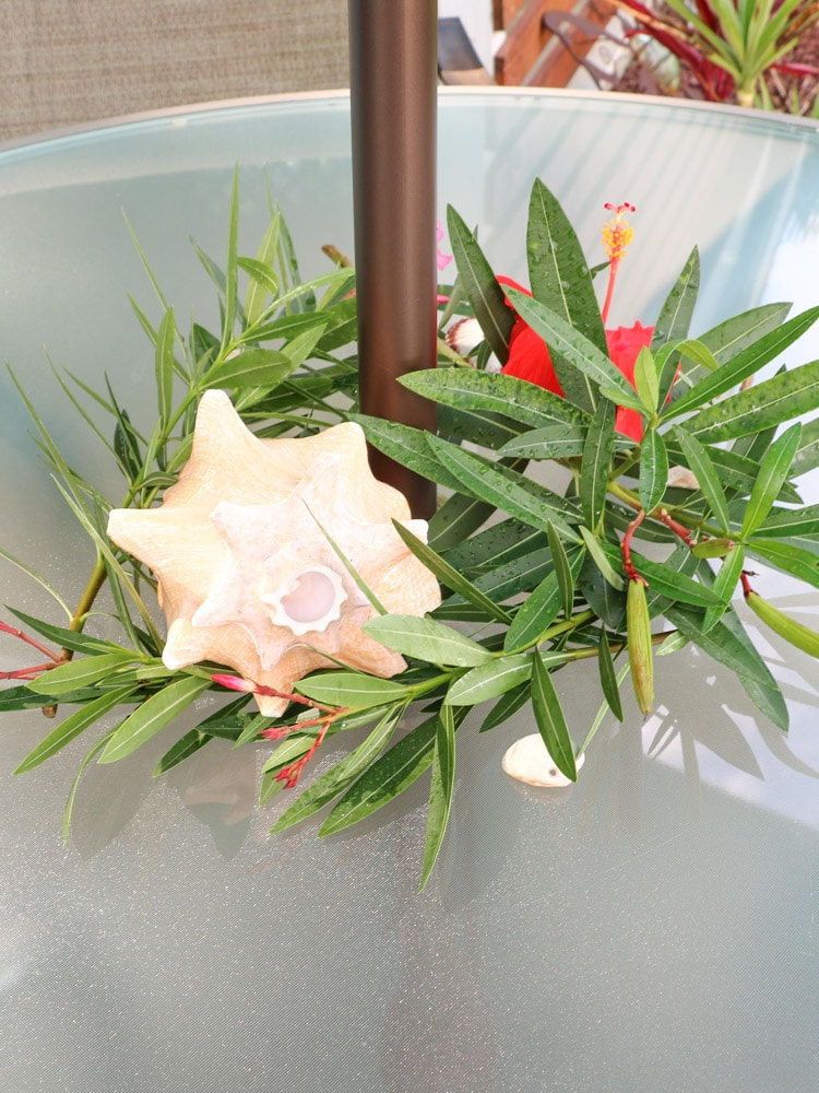A tropical center piece with leafs, a conch shell, and a hibiscus flower.