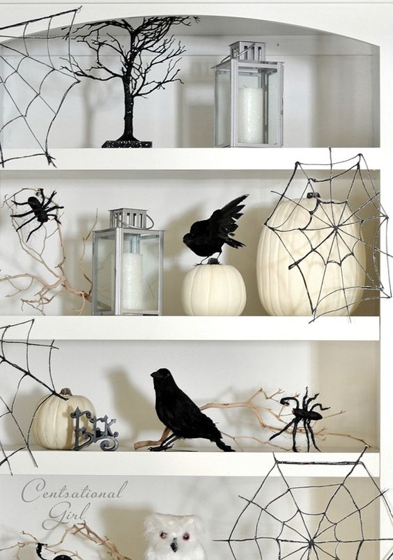 Easy to make Halloween decorations.  White shelves with black trees, spider webs and crows.  White pumpkins and silver lanterns.
