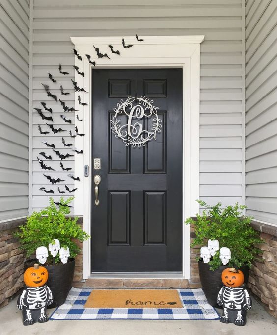 Easy to make Halloween decorations for your front porch and door.  Paper bats, layered rug of blue and white gingham and a home door mat, adorable skeletons with child like pumpkin heads.