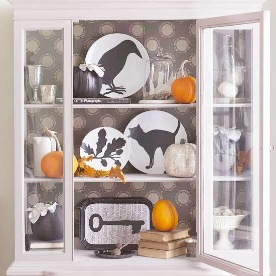 Easy to make Halloween decorations.  Beautiful white hutch with Halloween decoration ideas of plates with cats, leaves and crows silhouettes and small orange pumpkins.