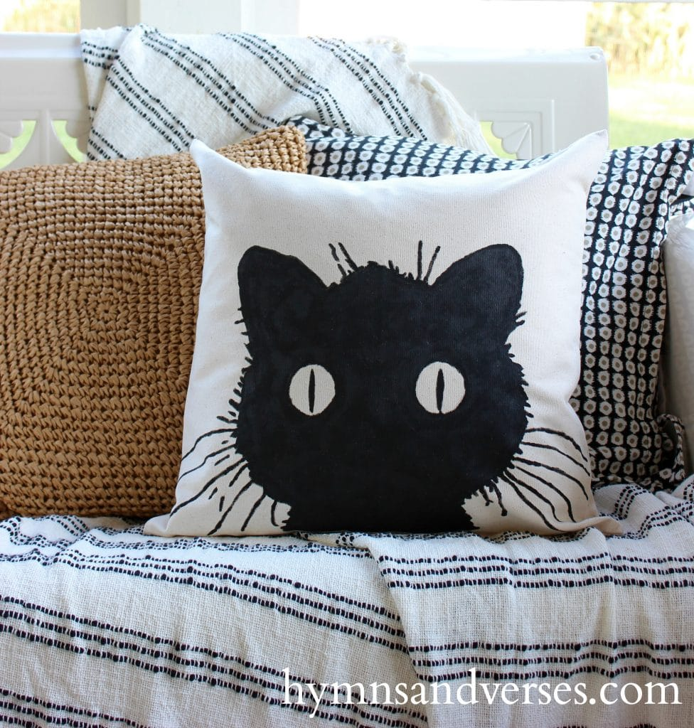 Cheap DIY Halloween decorations of a sweet white decorative pillow with a black cats face and it big round eyes.