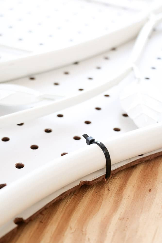 Upholstered headboards DIY by attaching a pegboard to a metal headboard with zip ties.
