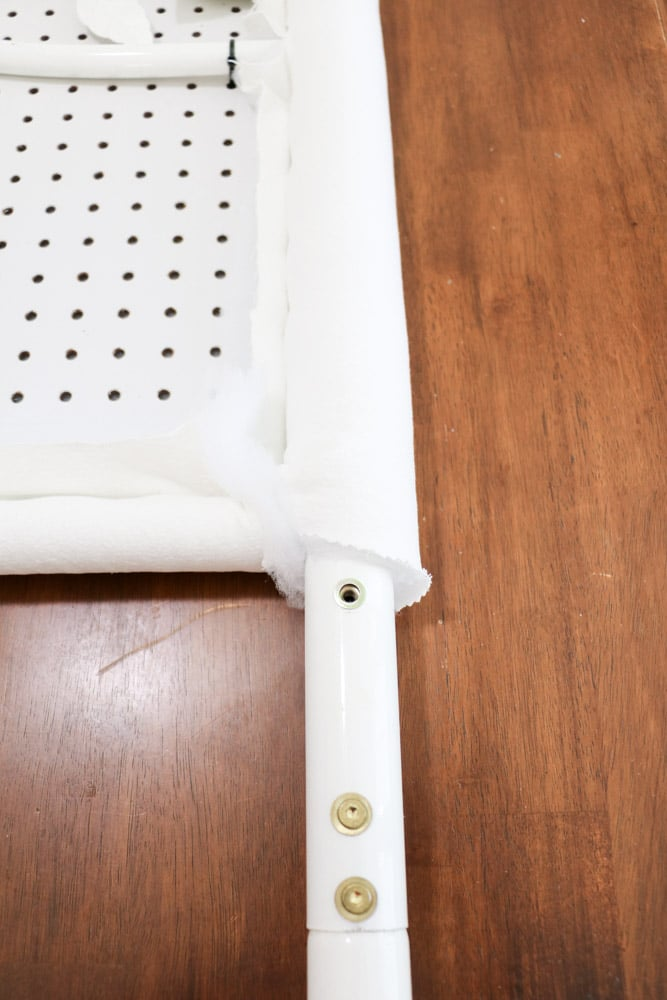 Wrap the fabric and quilt batting around the pegboard and metal bed frame to make an upholstered headboard.
