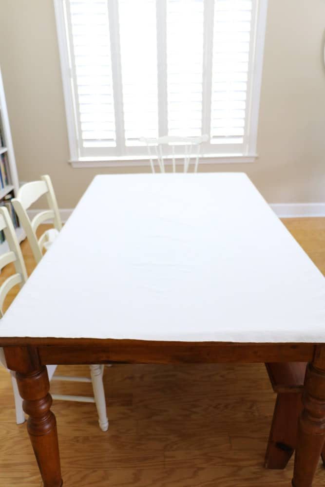 Lay the ironed drop cloth material on a table to make an upholstered headboard