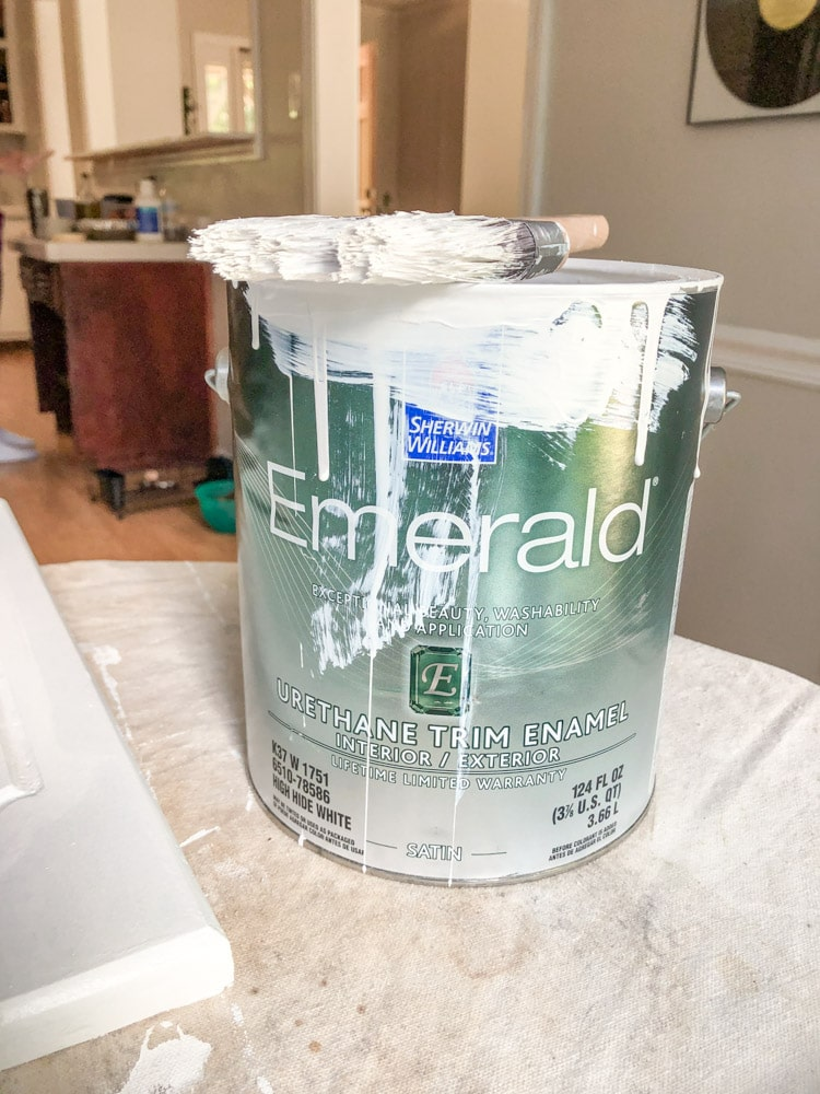 The Emerald Paint can with paint dripping down the side with the paint brush on top of it.