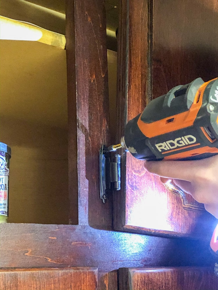 They are removing hinges from kitchen cabinets with a power drill, getting ready to paint them.