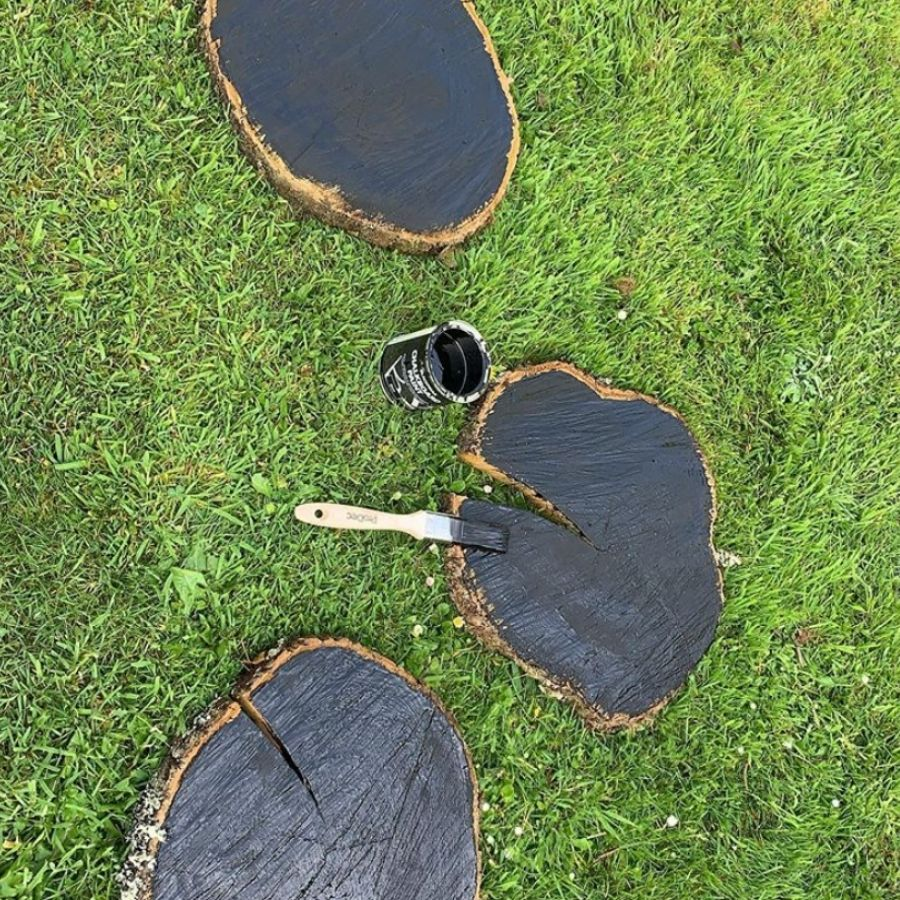 Slices of a wood log with raw edges are laying in the grass being painted with a black chalkboard paint.