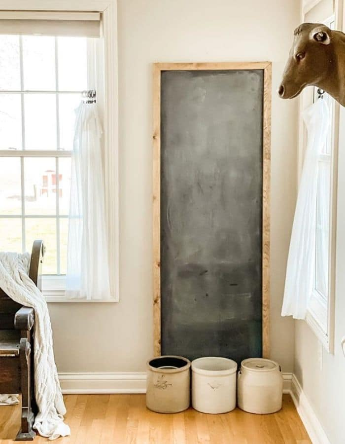 A vary tall farmhouse style chalk board leaning against a wall with 3 large crocks sitting at the base of the board.