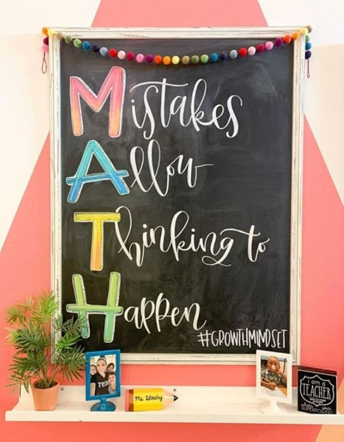 a long vertical chalkboard hanging with the text MATH, Mistakes Allow Thinking to Happen, written