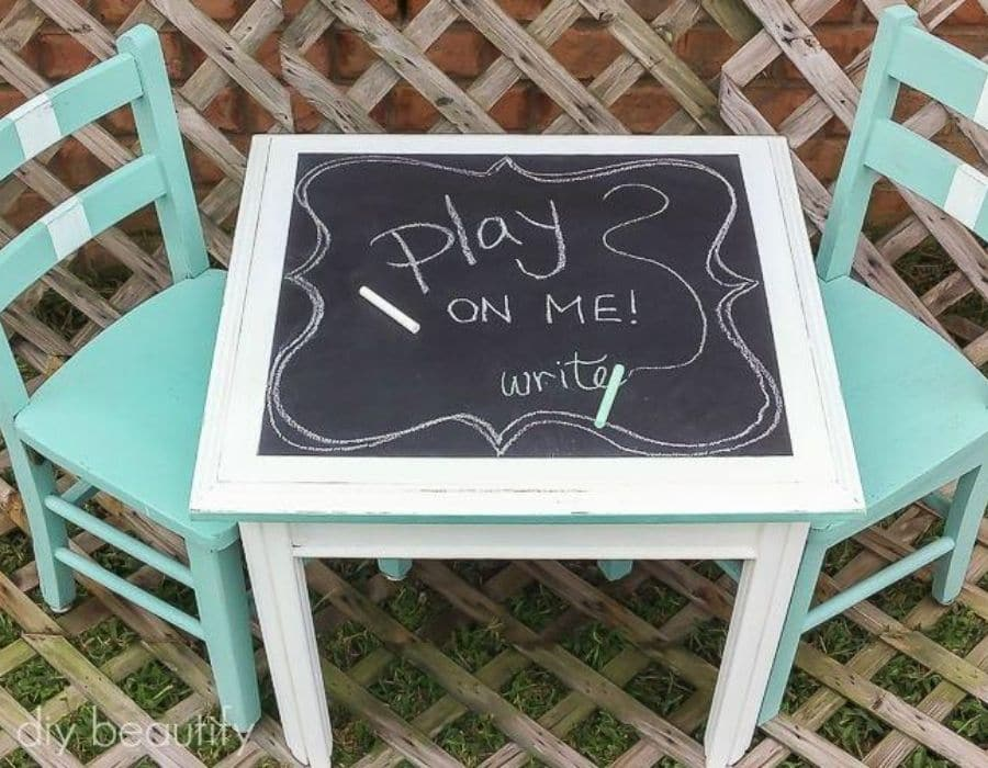 A little children table with 2 chairs, the top of the table was painted with chalkboard paint so that children can draw and write on the surface.