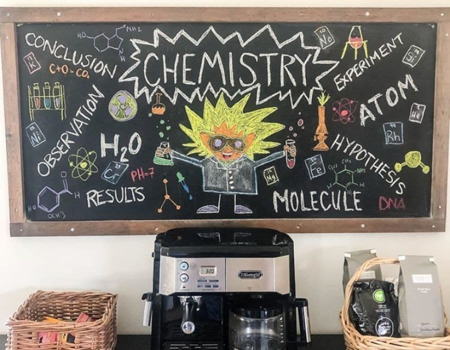 A long horizontal chalkboard for homeschool students, it is hanging on a wall above a coffee station with a coffee machine and some coffee as well.