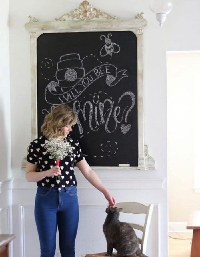 The chalkboard created in this post is behind a young woman holding a bouquet of baby breath flowers. She is gently petting her cat who is sitting in a chair next to her. The chalkboard says 'Will You Bee Mine?' written in chalk along with a drawing of a bee and its hive.