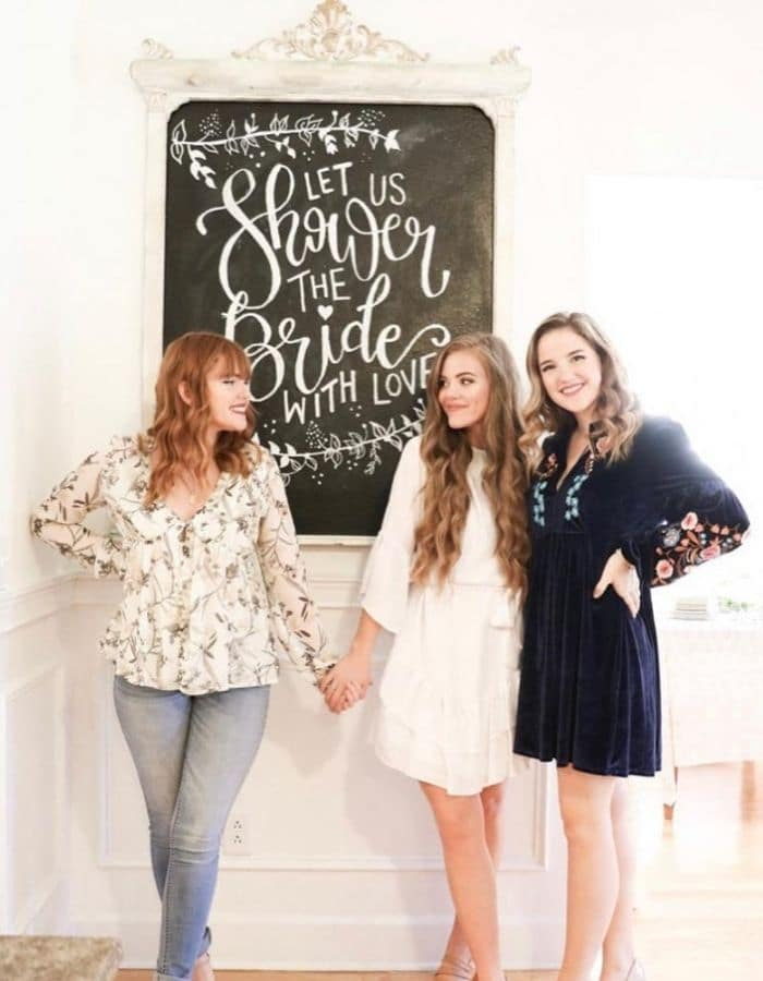 Three young woman holding hands in front of the chalkboard that was made in this post. The chalkboard says 'Let Us Shower The Bride With Love' written nicely in white chalk.