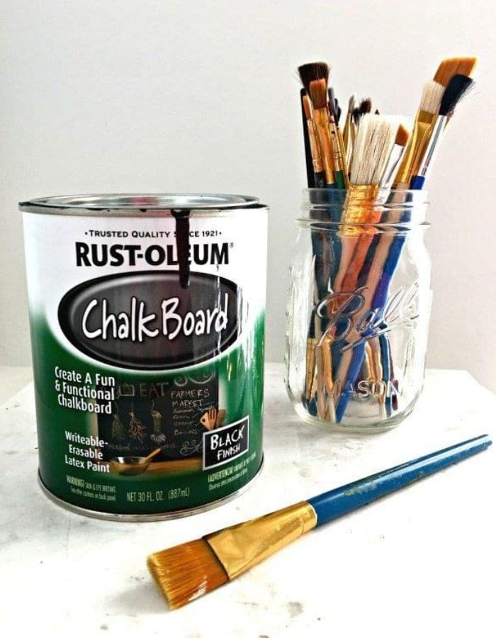 In this image there is a small can of Rust-Oleum Chalkboard Paint next to a mason jar full of artist paint brushes.