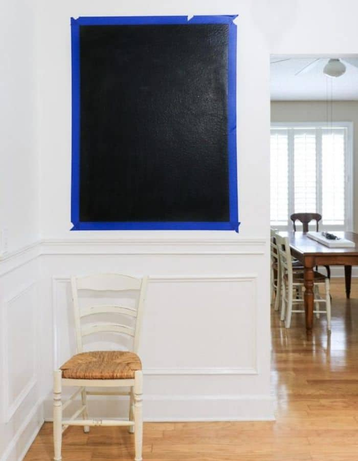 There is a small wall with a large rectangle of painters tape on the wall. Painted within the tape is a black chalkboard.